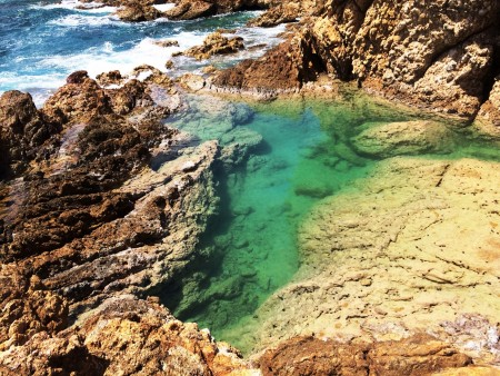 The contrast between the blue color of the Caribbean Sea against the greenish hue of the natural pools is stunning